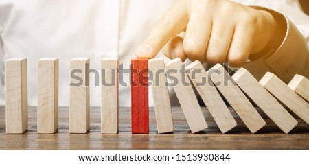 Businessman stops domino falling. Risk management concept. Successful strong business and problem solving. Reliable leader. Stop the destructive processes. Strategy development. Debt restructuring #1513930844