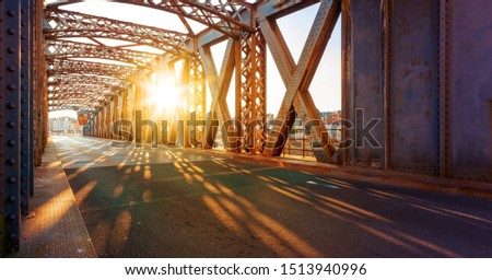 Asphalt road under the steel construction of a bridge in the city on a sunny day. Evening urban scene with the sunbeam in the tunnel. City life, transport and traffic concept. #1513940996