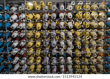Thread spools of an industrial weaving loom for fabrication of fabrics. #1513945124