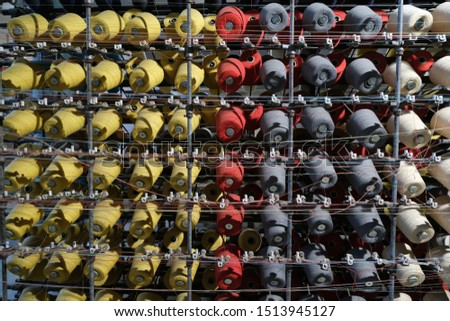 Thread spools of an industrial weaving loom for fabrication of fabrics. #1513945127