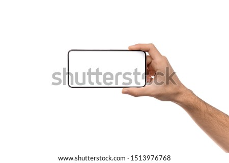 Man's hand holding modern smartphone with blank screen in horizontal orientation for mockup, copy space Royalty-Free Stock Photo #1513976768