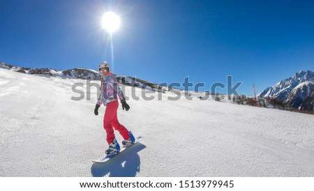 A snowboarder going down the slope in Heiligenblut, Austria. Perfectly groomed slopes. High mountains surrounding the girl, wearing pink trousers and colorful jacket. Girl wears helm for protection #1513979945