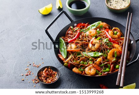 Stir fry noodles with vegetables and shrimps in black iron pan. Grey background. Copy space. #1513999268
