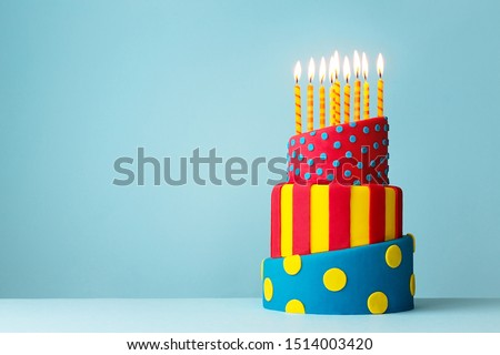 Colorful topsy turvy birthday cake with candles #1514003420