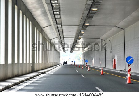 Road tunnel in mountains. Mountain road tunnel with luminous safety lights and yellow road line. Tunnel on the highway.  Automobile trip. Pathway with tunnel. Drive through the mountain #1514006489