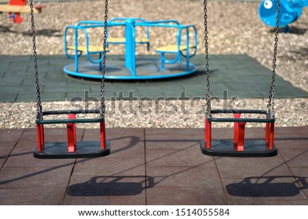 Two rubber swings weigh on a chain. Playground on a sunny day, shadow from the swing. Seats on the swing are free, there are no children on the Playground #1514055584