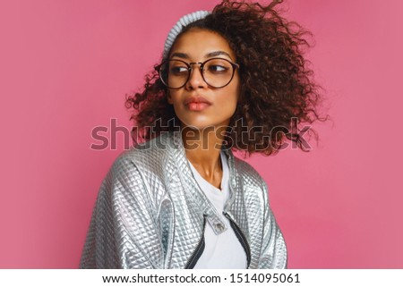 Close up fashion portrait of  mix race woman with brown skin and curly African hairstyle on vivid pink background. Wearing silver winter  jacket and grey hat.  #1514095061