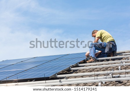 Installing solar photovoltaic panel system. Solar panel technician installing solar panels on roof. Alternative energy ecological concept. #1514179241