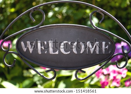 iron welcome sign in the garden with hydrangea on the background