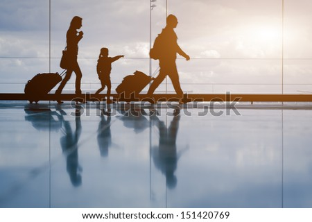 Silhouette of young family with luggage walking at airport, girl showing something through the window Royalty-Free Stock Photo #151420769