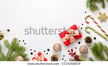 Christmas frame red flat lay with presents, golden elements, candy canes, confetti. Christmas template on white wood #1514266859