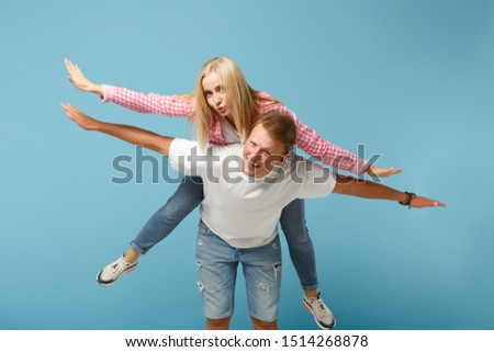 Young fun couple two friends guy girl in white pink empty blank design tshirts posing isolated on pastel blue background studio portrait. People lifestyle concept. Mock up copy space. sitting on back #1514268878