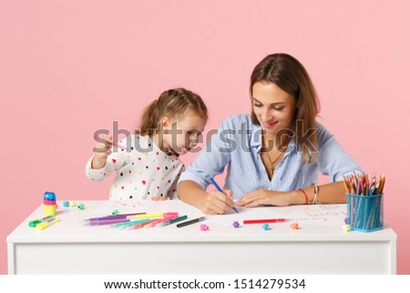 Woman child baby girl 4-5 years old draws are engaged in creativity. Mommy little kid daughter isolated on pastel pink background studio portrait. Mother Day love family parenthood childhood concept