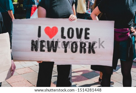 """The phrase """" I love New York """" and red heart icon drawn on a black carton banner in woman hands. Woman in black dress and with black hair holds a cardboard with an inscription: I love New York"""