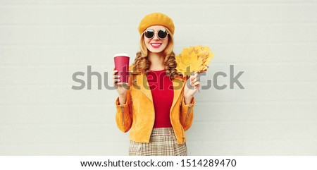 Portrait stylish happy smiling woman with yellow maple leaves, coffee cup in french beret posing over gray wall background #1514289470