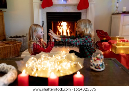 Side view of young Caucasian brother and sister sitting by the fireplace in their sitting room at Christmas time playing #1514325575