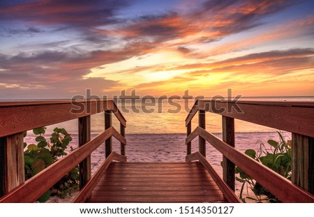 Boardwalk leading to a Sunset over North Gulf Shore Beach along the coastline of Naples, Florida Royalty-Free Stock Photo #1514350127