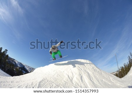 A snowboarder jumps on snow pile #1514357993