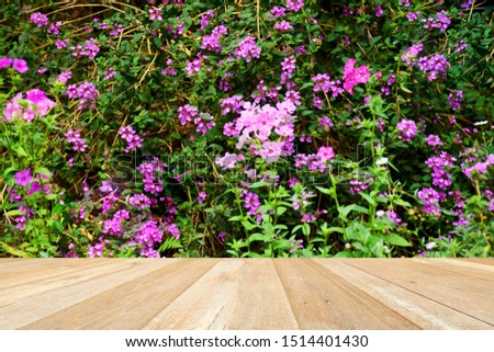 Empty top wooden table on closeup beautiful flowers blooming in garden #1514401430
