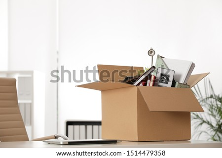 Cardboard box full of stuff on table in office #1514479358