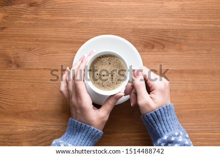 Coffee break and fall mood. Female hands in sleeves of cozy blue pullover hold white cup of classic coffee, top view, close up. Hygge, relaxing, home, cosiness, warmth, breakfest and eco style concept #1514488742