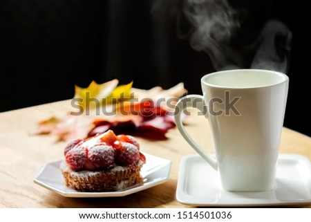 Overcast autumn overcast restored with a cup of hot coffee on the table and a sweet berry dessert #1514501036