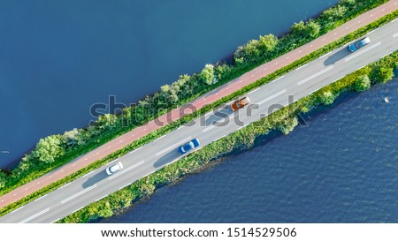 Aerial drone view of motorway road and cycling path on polder dam, cars traffic from above, North Holland, Netherlands #1514529506