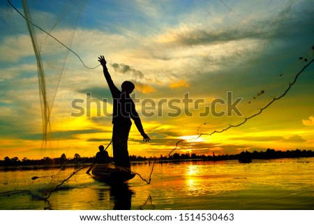 Two local fishermen trying to find fish to feed their families In which one person paddles the other, casting a net in the river at dusk at dusk #1514530463