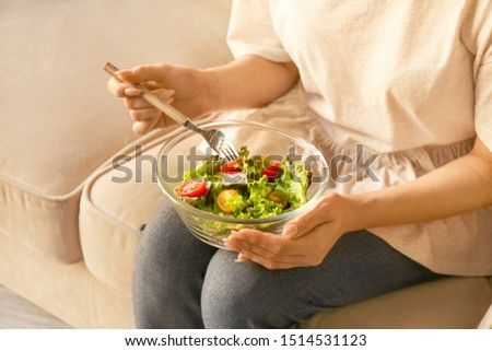 Woman eating tasty vegetable salad at home, closeup #1514531123