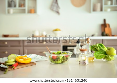 Bowl with salad and ingredients on kitchen table #1514531240