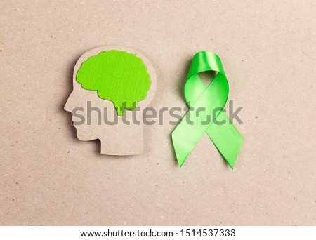 World mental health day concept. Green awareness ribbon and brain symbol on a brown background. Royalty-Free Stock Photo #1514537333