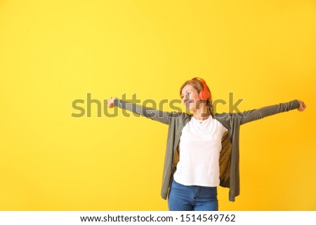 Beautiful young woman listening to music on color background #1514549762