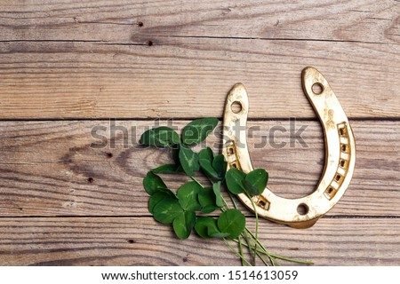 St.Patrick's Day. Golden horseshoes with clover leafs on wooden background. Copy space, top view.