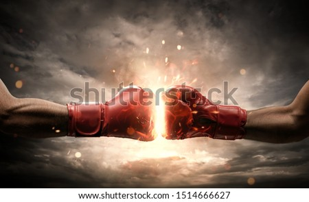 Boxing fight, close up of two fists hitting each other over dark, dramatic sky with copy space Royalty-Free Stock Photo #1514666627