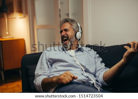 mid aged man listening music and singing at his home #1514723504