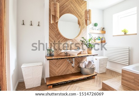 White sink on wood counter with a round mirror hanging above it. Bathroom interior. Royalty-Free Stock Photo #1514726069