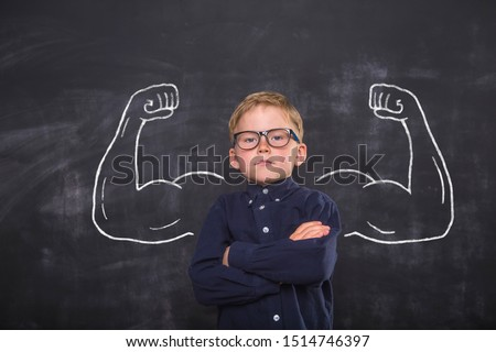 Cute child boy in school uniform and glasses. Go to school for the first time. Child with school bag and books. Kid in class room near chalkboard with muscles on it. Back to school #1514746397