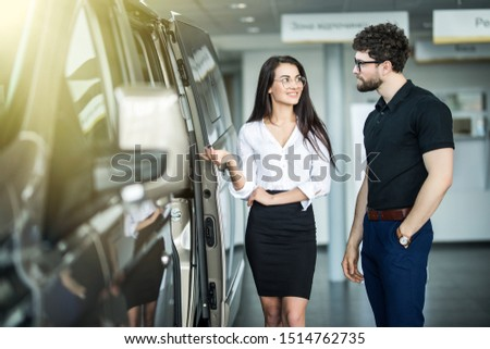 Young saleswoman working with client in car dealership #1514762735