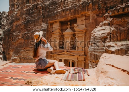 Aerial view of young woman tourist sitting on a cliff after reaching the top, Al Khazneh in the ancient city of Petra, Jordan, UNESCO World Heritage Site #1514764328