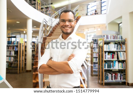 Smiling African American man posing at public library. Front view of confident young guy with crossed arms standing in front of stairs. Knowledge concept #1514779994
