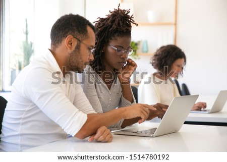Instructor explaining corporate software specific to intern. Man and woman in casual sitting at desk in classroom, working on laptop, pointing at screen, talking. Education concept #1514780192