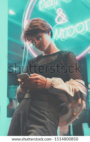 Fashion tomboy teen hipster short hairstyle gen z girl wear stylish clothes glasses stand near neon street sign in night city using cellphone mobile apps texting messages social media looking at cell