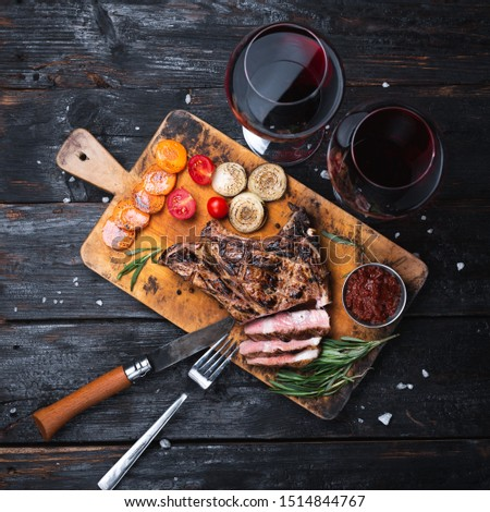 grilled pork steak on a cutting board, delicious pieces of meat, a glass of red wine. Dinner for two #1514844767