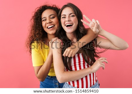 Image of happy multinational girls hugging and showing peace sign isolated over pink background #1514859410