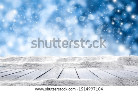 Wooden background of table with snow decoration and free space for your product. Blue blurred background of snowflakes and frost. Christmas time photo .  #1514997104