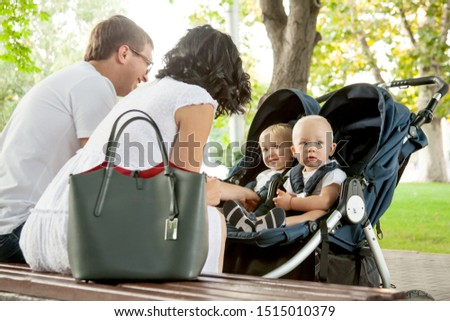 happy family walking with twin on city park. the parent sit on the bench and communicate with kids on buggy. #1515010379