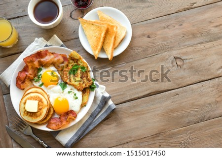 Full American Breakfast on wooden, top view, copy space. Sunny side fried eggs, roasted bacon, hash brown, pancakes, orange juice and coffee for breakfast. #1515017450