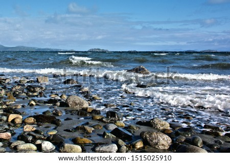 A beautiful low angle view of illuminated rocks and stones along the sandy beach with exposed rocks during low tide #1515025910