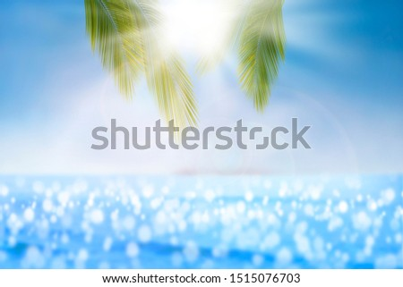 Blur image, beautiful nature green palm leaf  on Tropical sand beach with palm leaves,lake with white sand and green water With Palm leaves like Maldives. for display products and background