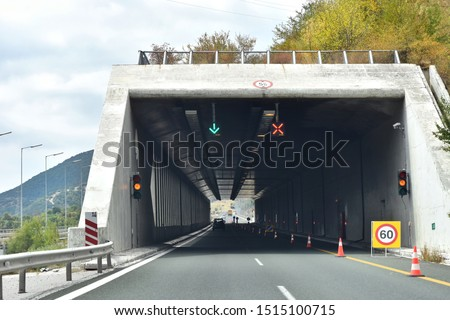 Road tunnel in mountains. Mountain road tunnel with luminous safety lights and yellow road line. Tunnel on the highway.  Automobile trip. Pathway with tunnel. Drive through the mountain #1515100715